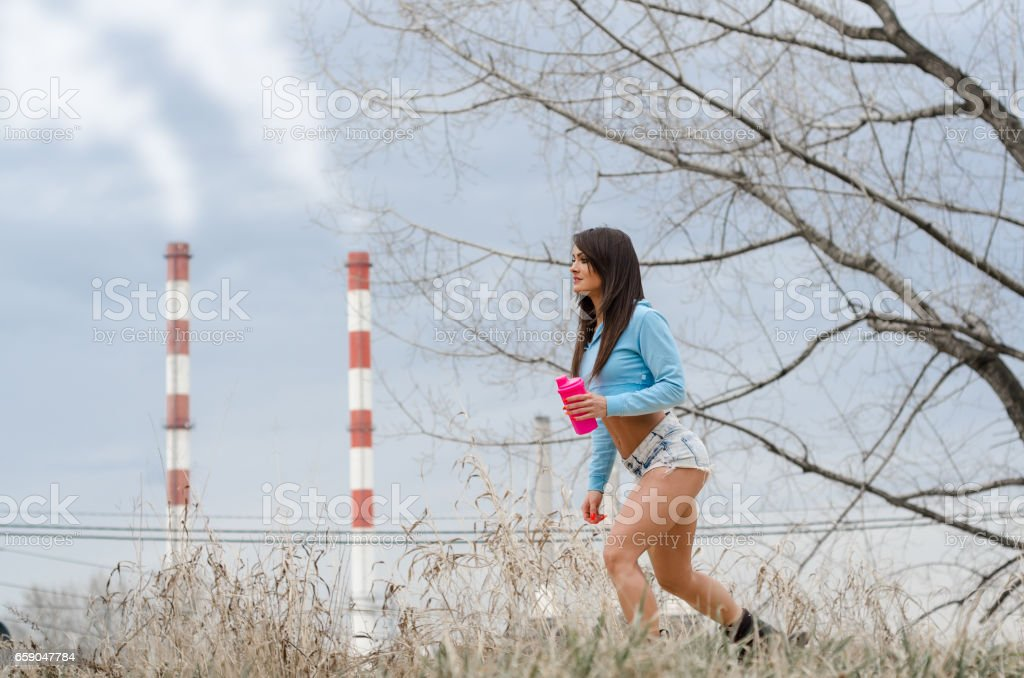 Girl rides roller skates in front of factories and polluted chimneys, sport against pollution stock photo