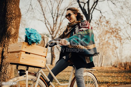 Girl riding a bike and carrying a bouquet of blue flowers in the basket
