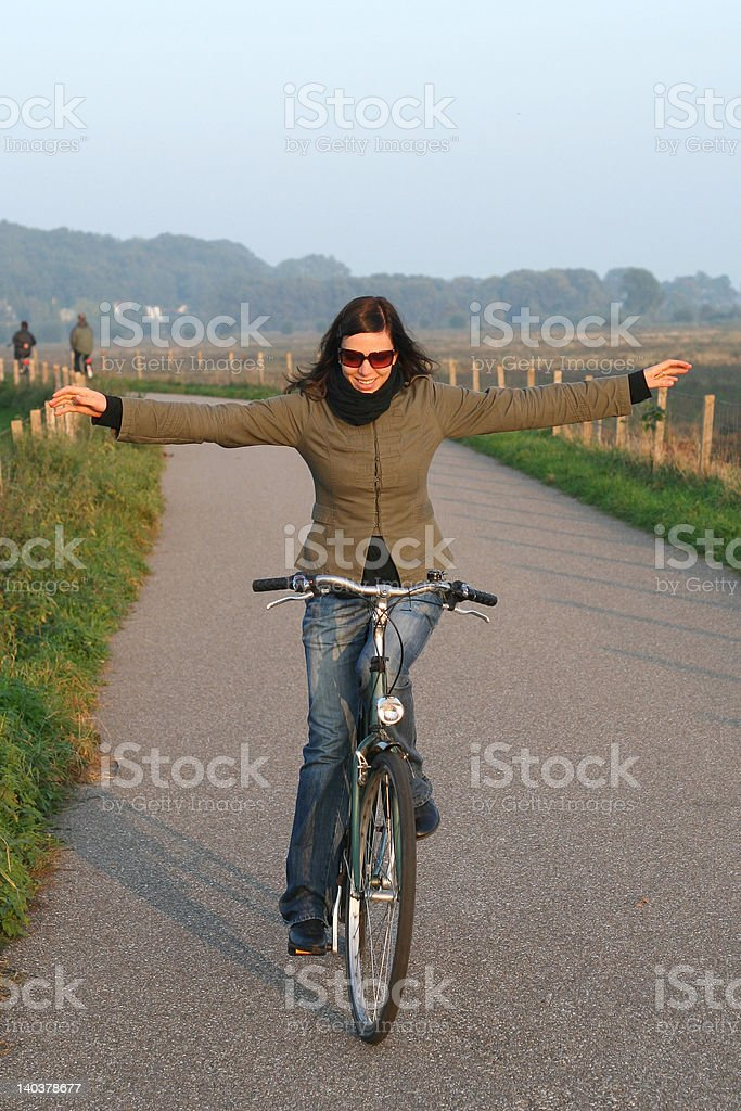 Girl riding a bike with stretched aside arms stock photo