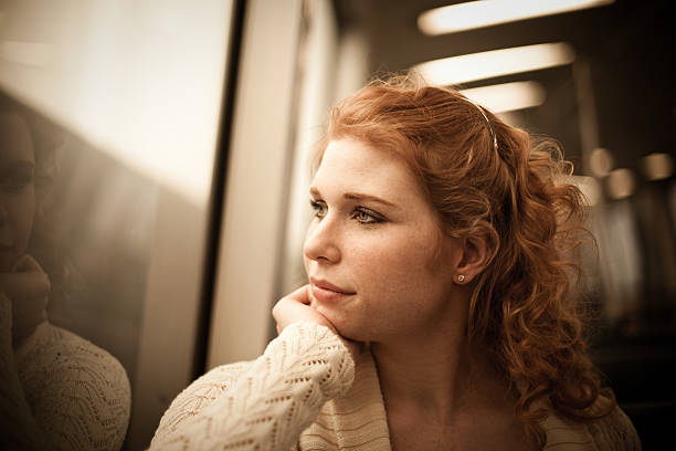 Girl Riding a Commuter Rail Train A girl riding a Bay Area Rapid Transit train looks out the window desaturated stock pictures, royalty-free photos & images