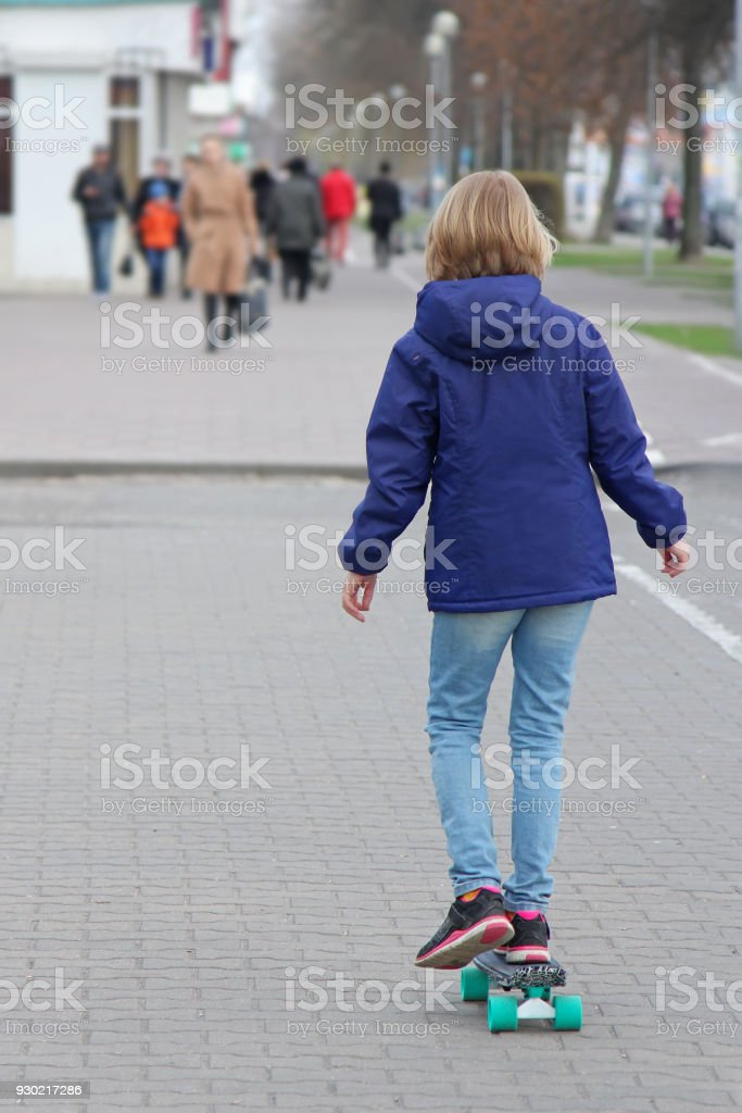 Girl riding a skateboard on a city street. A child of a pre-teen age on a walk. View from the back. stock photo