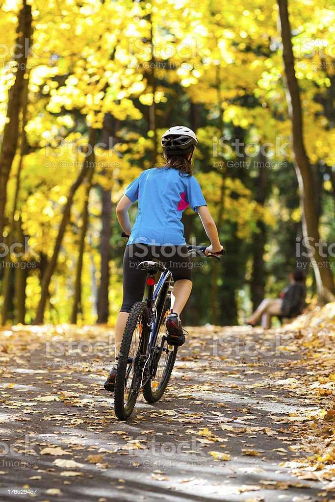 Girl riding bike in city park royalty-free stock photo