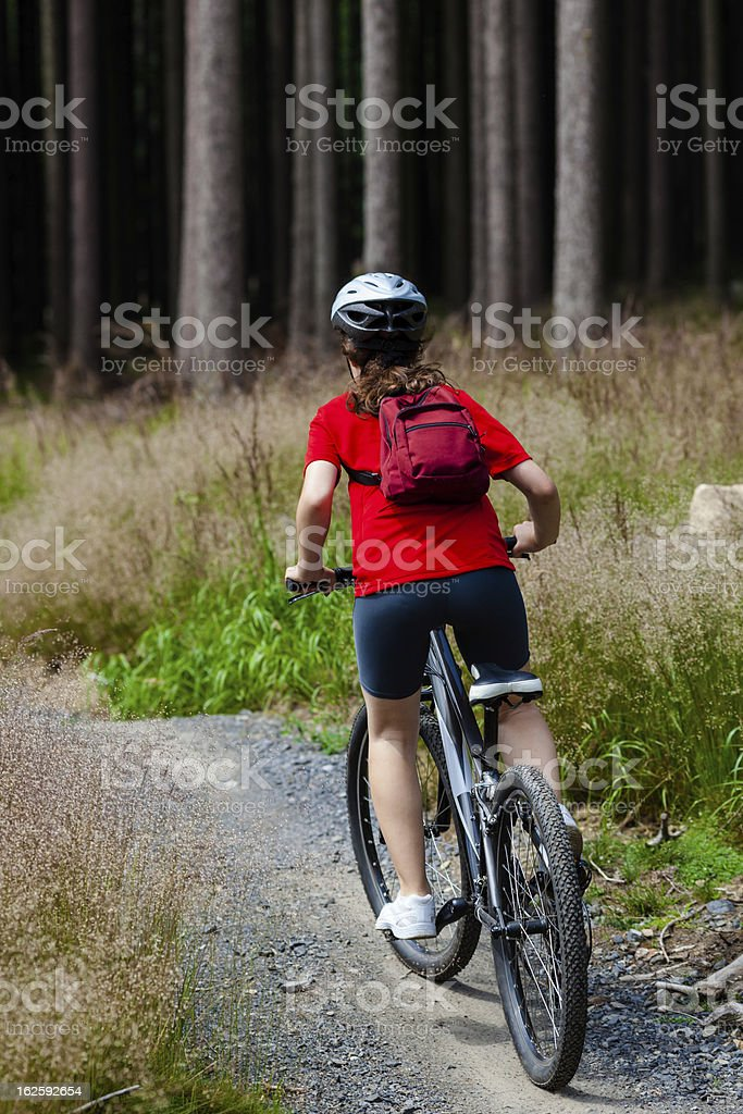 Girl riding bike in forest royalty-free stock photo