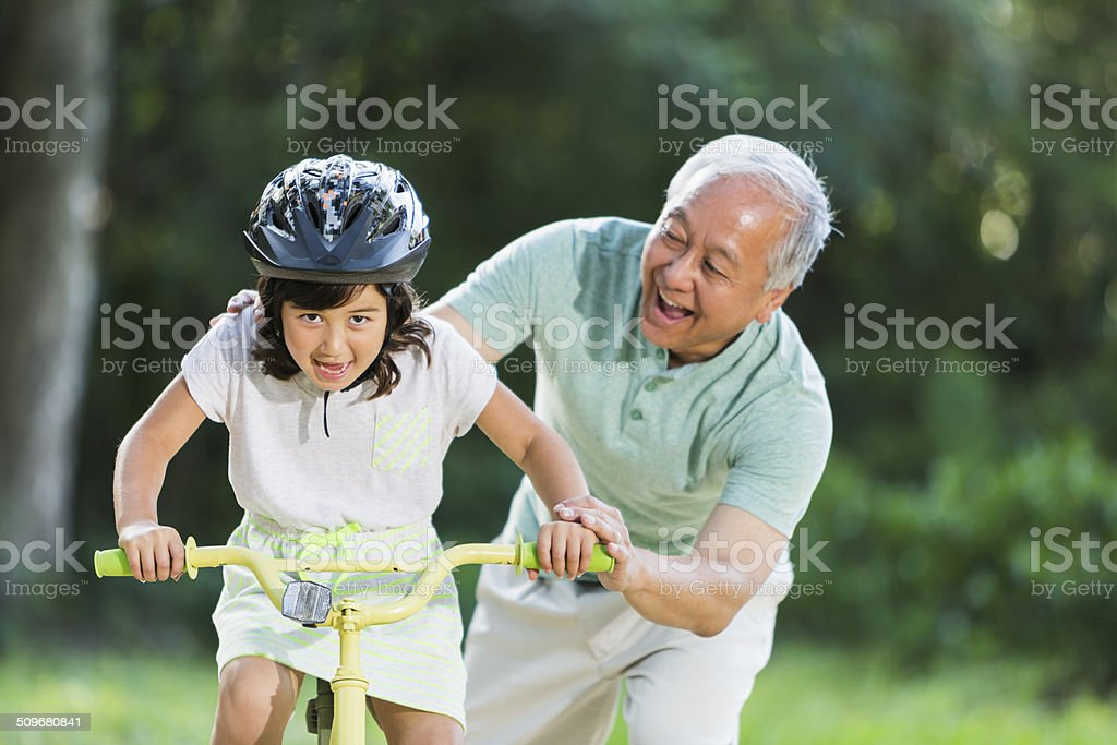 Girl riding bike, with grandfather stock photo