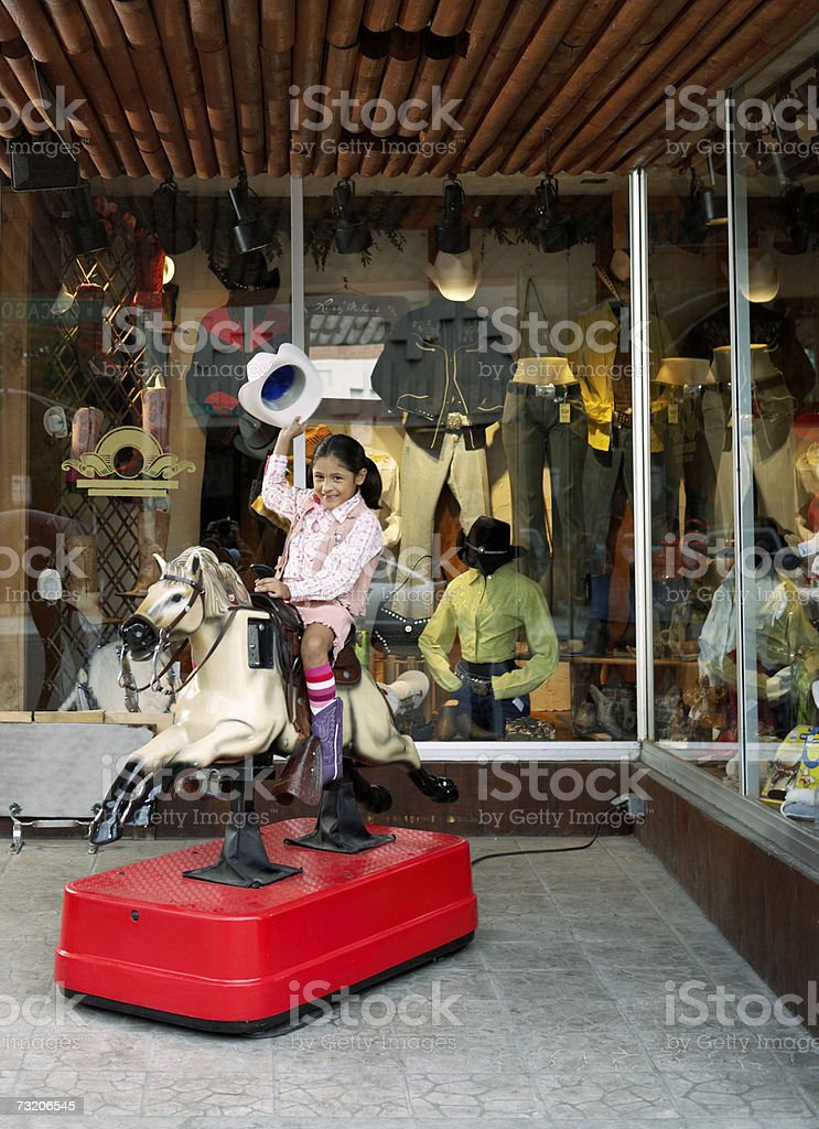 Girl (6-8) riding on coin operated horse outside store stock photo