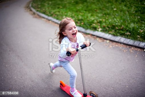 istock Girl riding push scooter 617584036