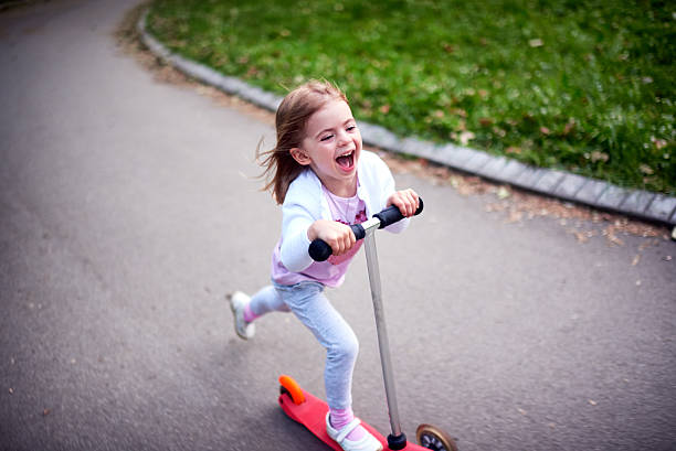 Girl riding push scooter – Foto