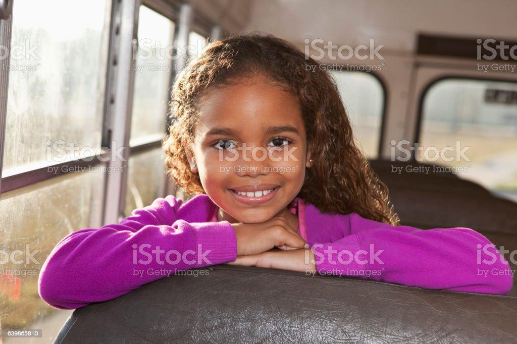 Girl riding school bus stock photo