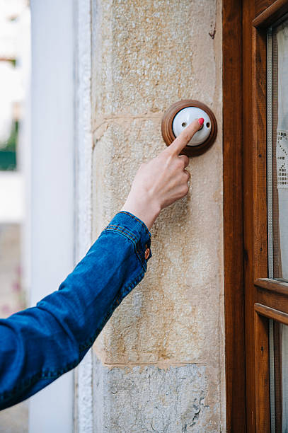 Girl rings the doorbell stock photo