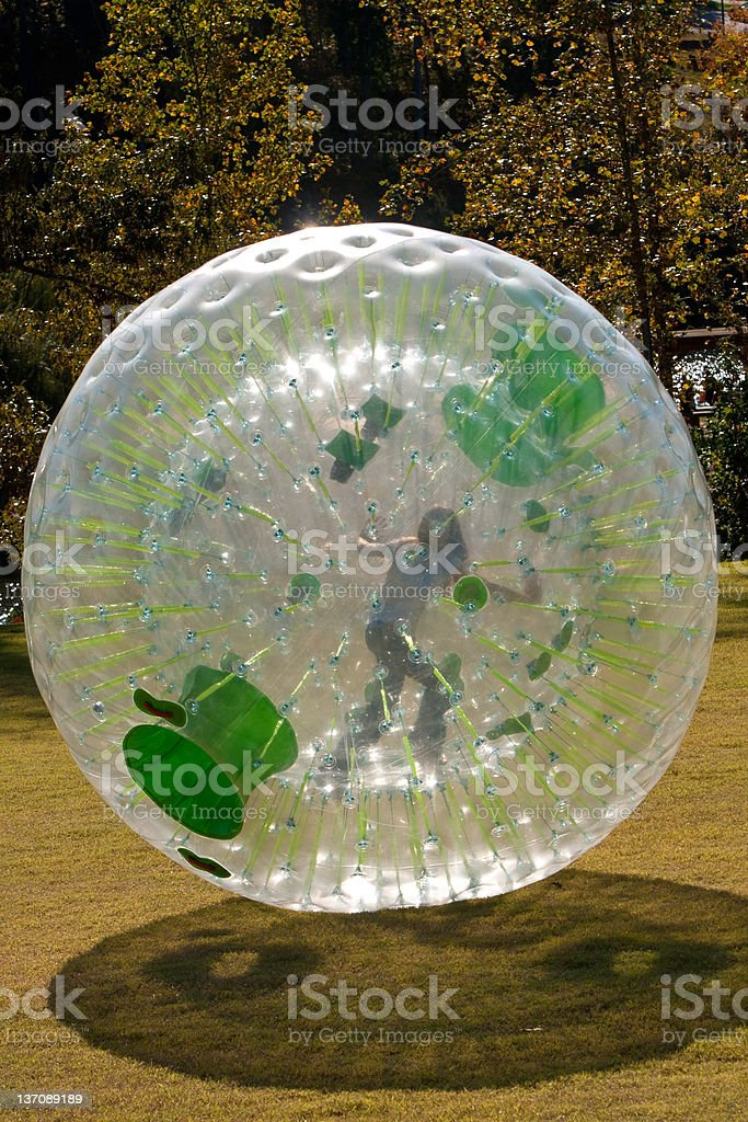 Girl Rolling Inside Large Plastic Ball stock photo