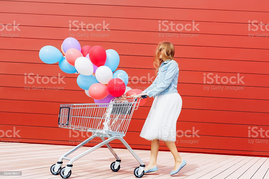 girl rolling shopping cart with balloons stock photo