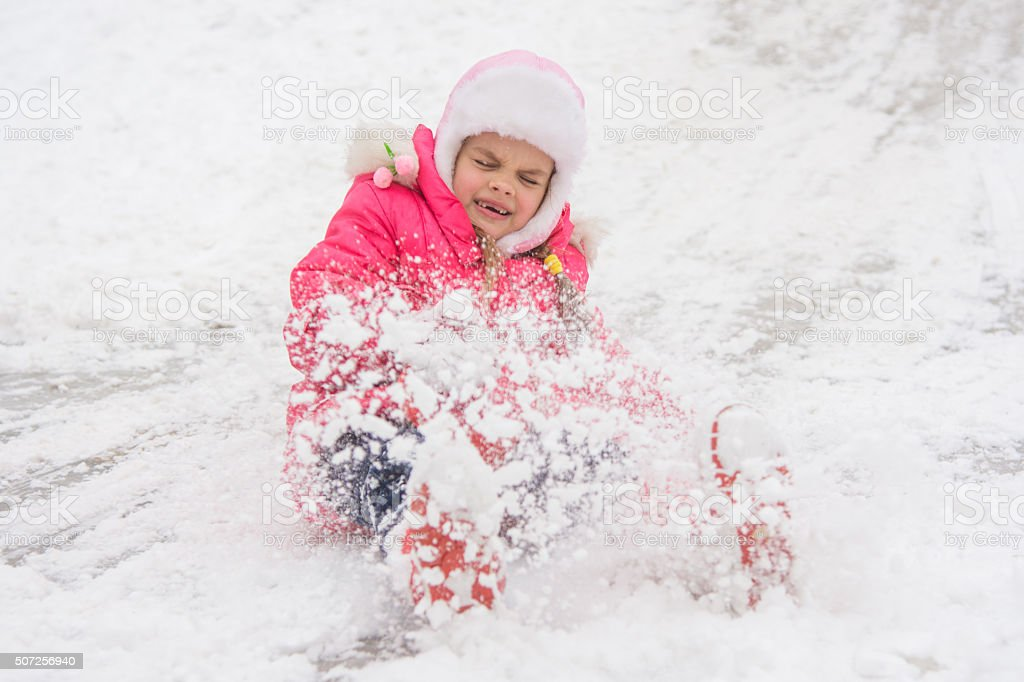 Girl rolls down hill snow closed her eyes came boots stock photo