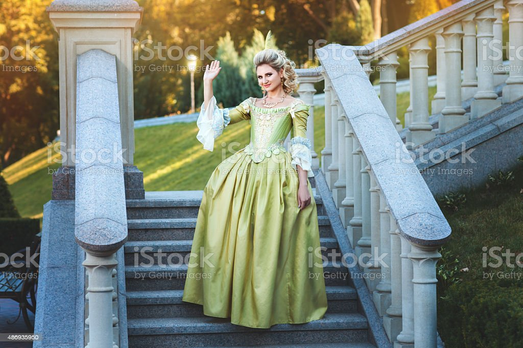 Girl royal dress standing steps of the palace. stock photo