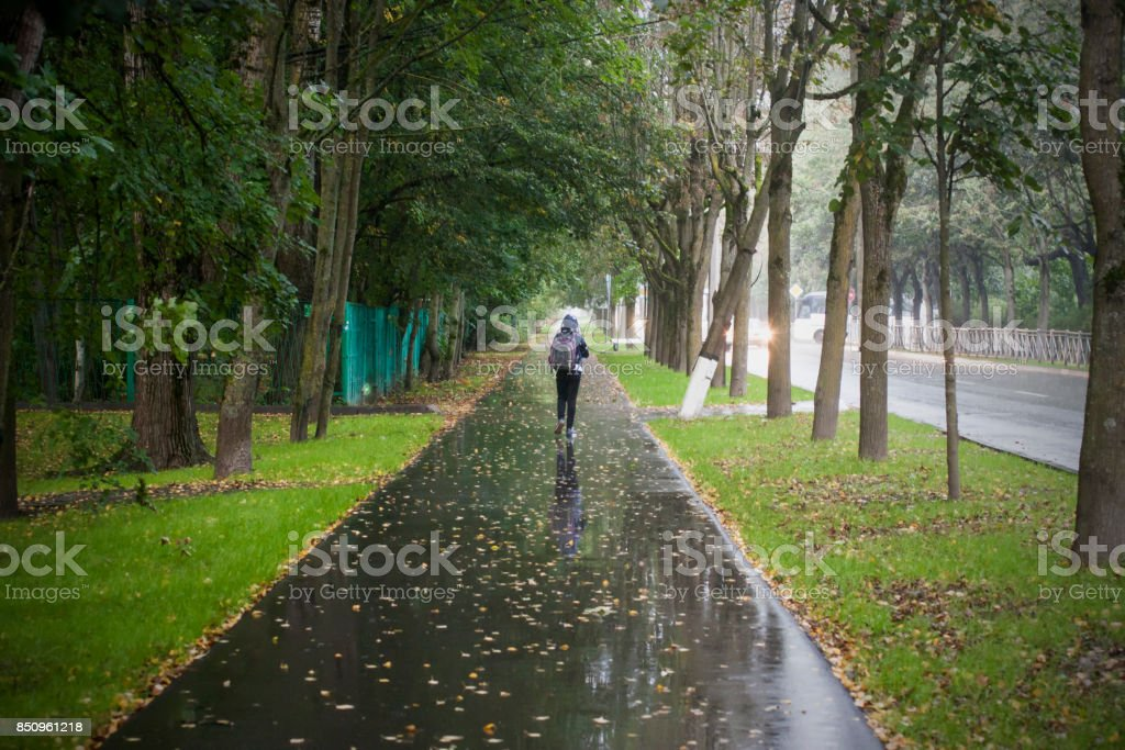 Girl run on wet path during rain stock photo