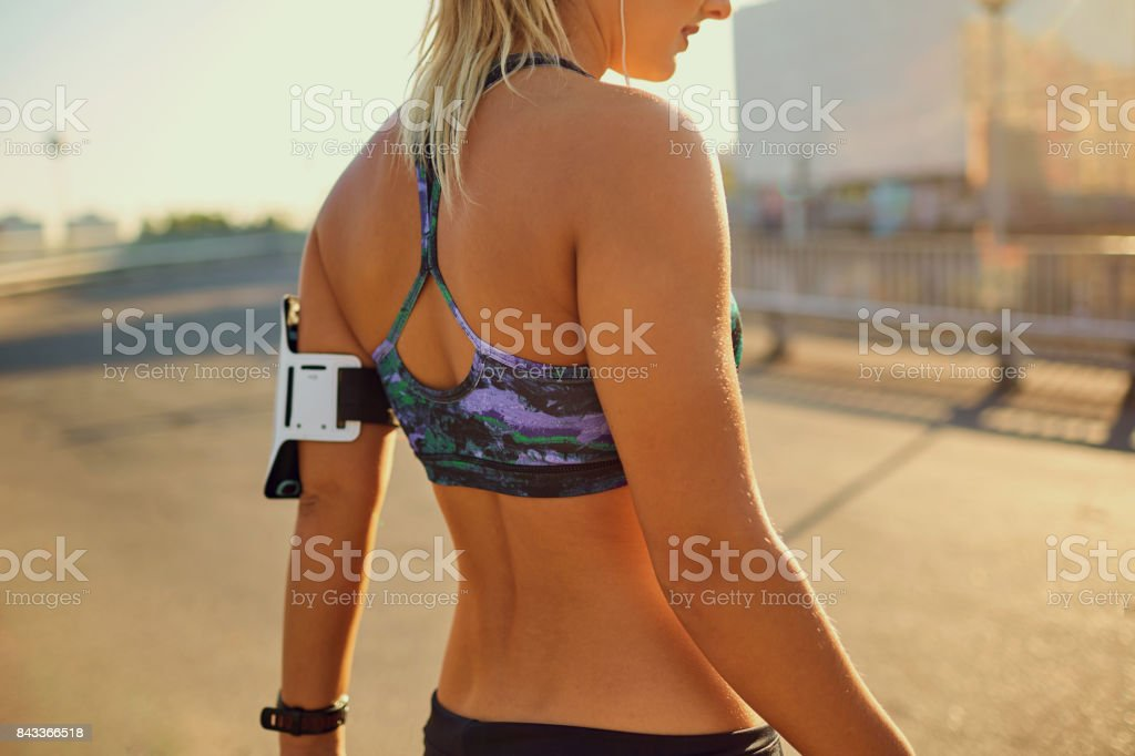Girl runner before jogging on the road in the city in the summer stock photo