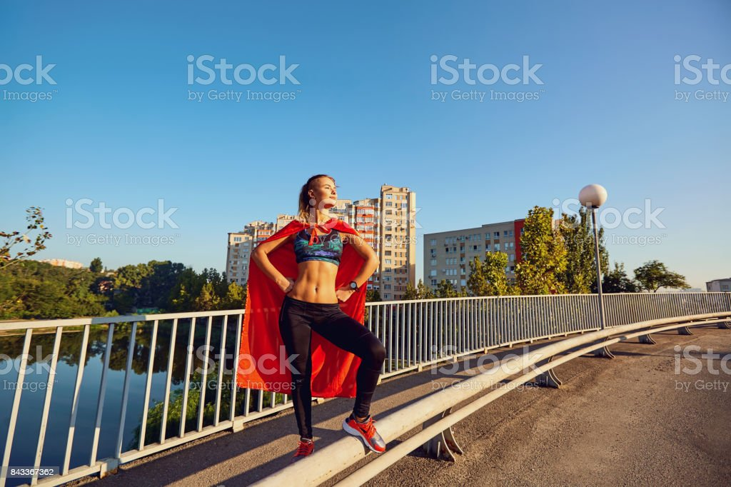 Girl runner in a superhero costume on the road in the city. stock photo