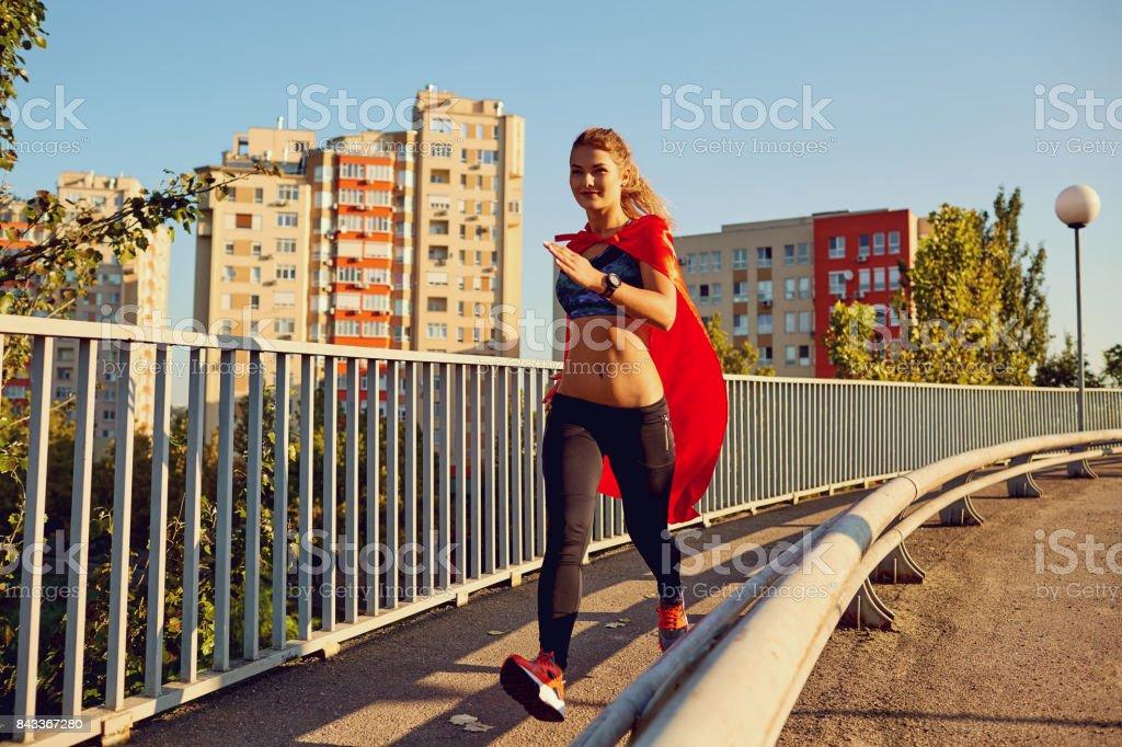 Girl runner in a superhero costume runs along the road. stock photo