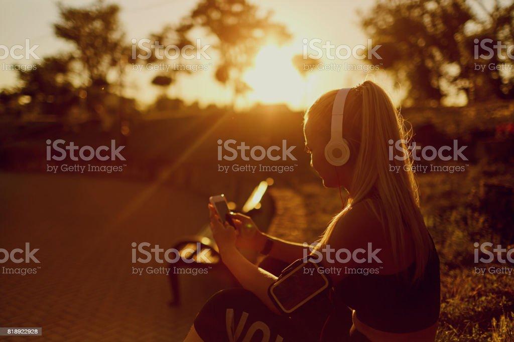 Girl runner listening to music in the park stock photo