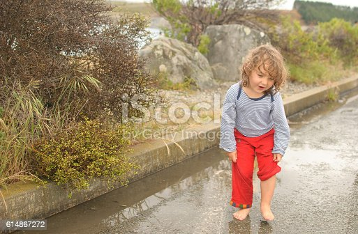 istock Girl running and playing in puddle 614867272