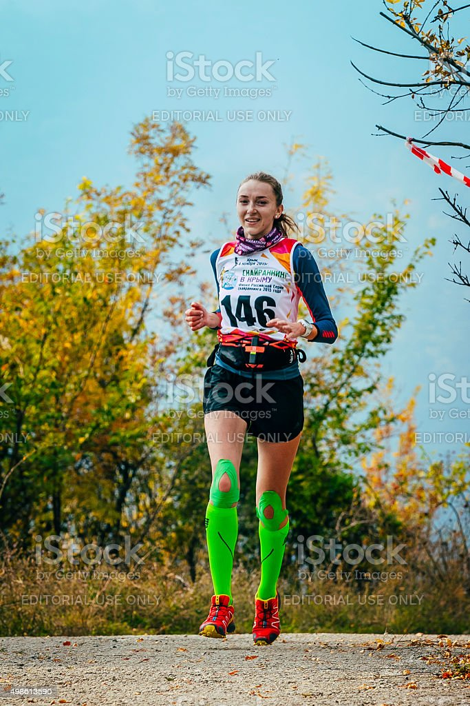 girl running autumn forest compression socks and kinesio tape knees stock photo