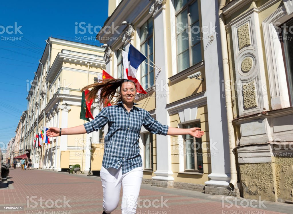 girl running down the street on a Sunny day with his hands outstretched, in the background of the building and the flags, the girl in the city, a young woman smiling zbiór zdjęć royalty-free