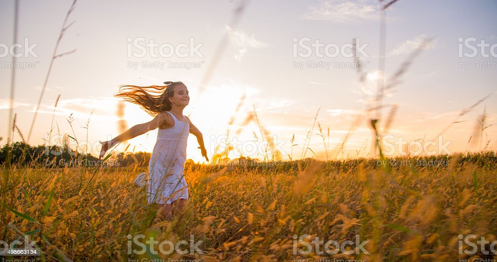 Girl Running In A Meadow At Sunset stock photo