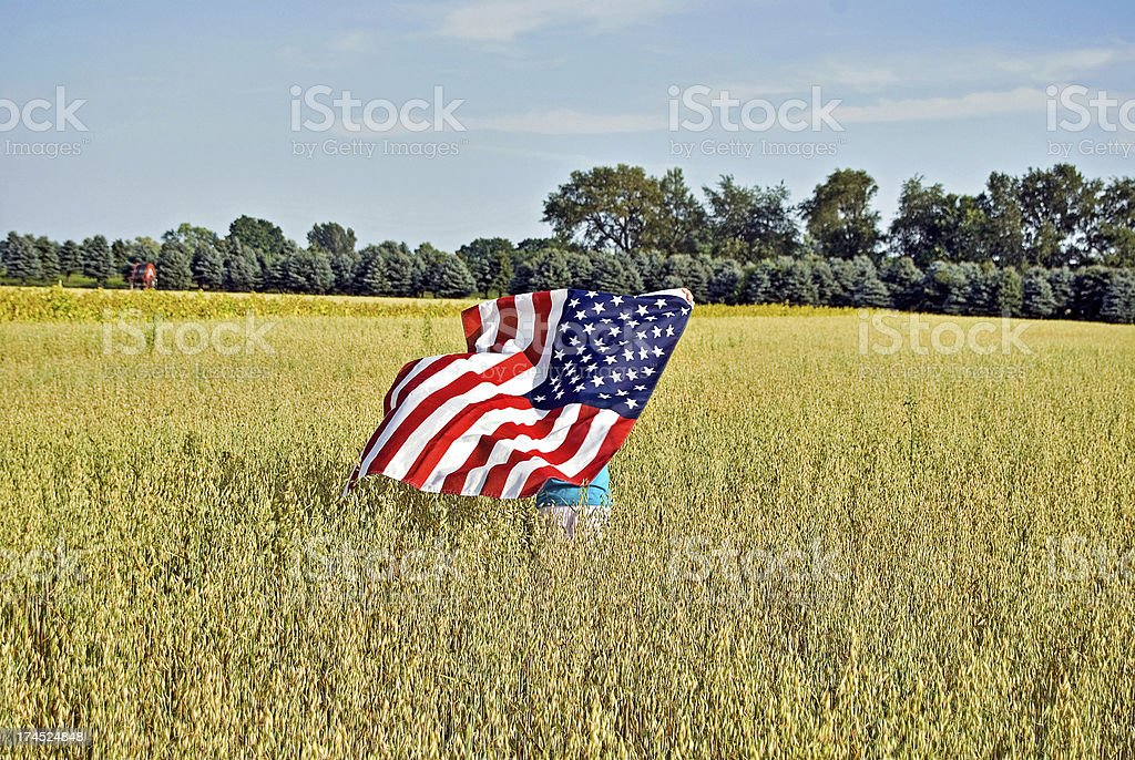 girl running in field with flag stock photo