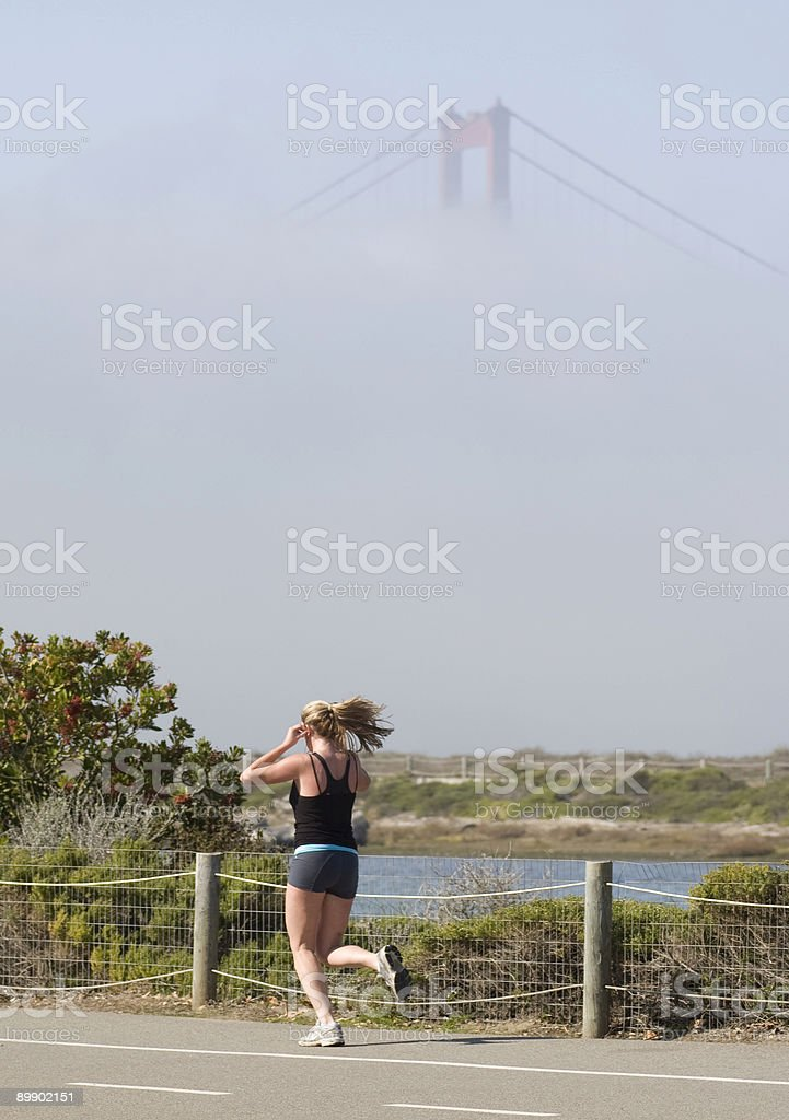 Girl running in front of Golden Gate bridge royalty-free stock photo