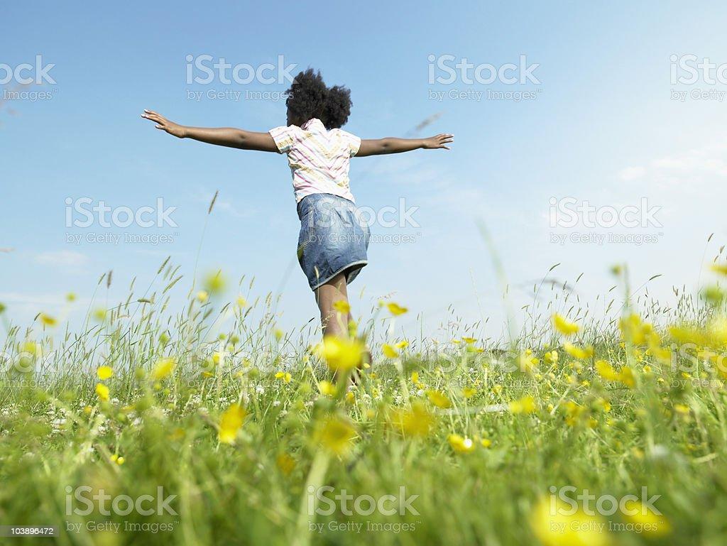 Girl running in grass stock photo