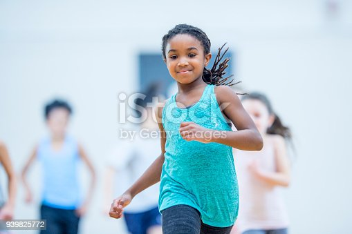 An african american girl runs and smiles at the forefront of a group of kids in her elementary physical education class.