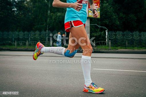 Omsk, Russia -  September 20, 2015: Girl running marathon, knees in blue kinesiology taping during Siberian international marathon
