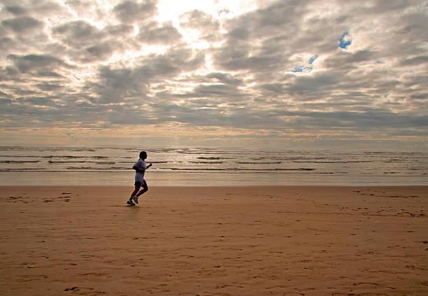 Girl running on a beach stock photo