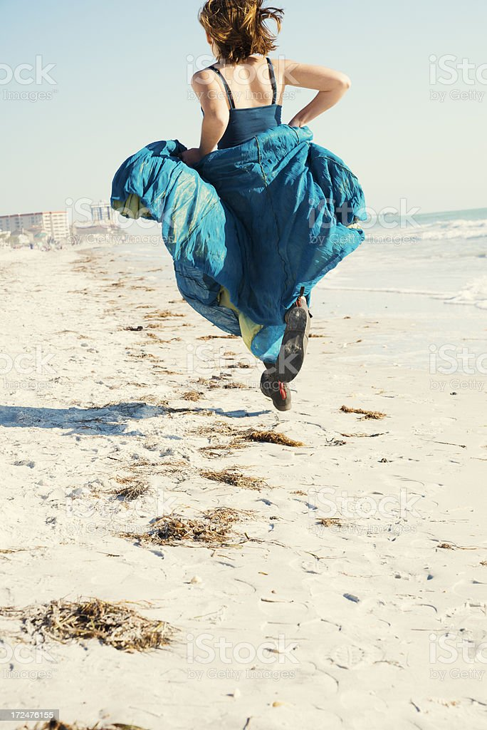 Girl running on beach with long skirt and boots royalty-free stock photo