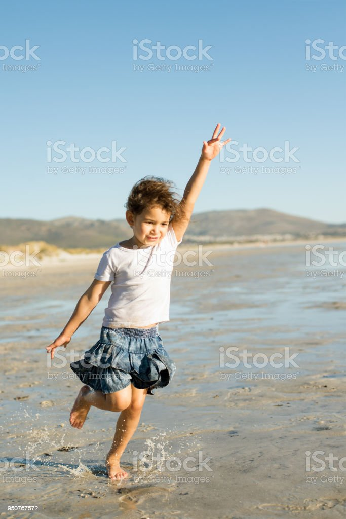Girl running on the beach with her arms outstretched as though she's flying stock photo