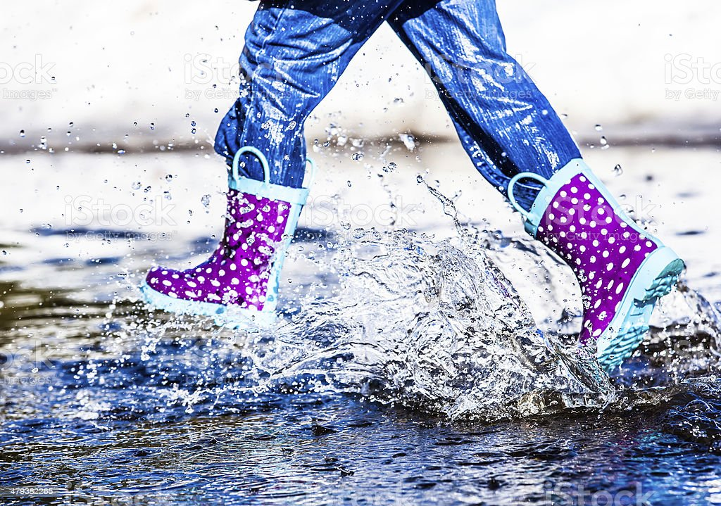 Girl Running Through Puddle stock photo