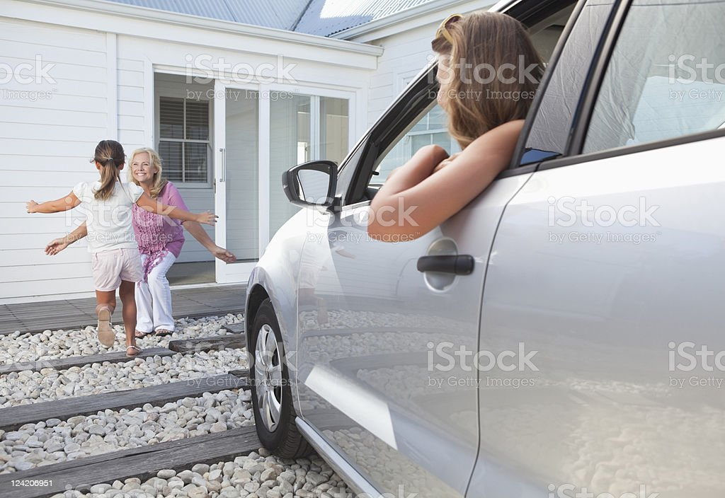 Girl running to hug grandmother with mother in car looking on royalty-free stock photo