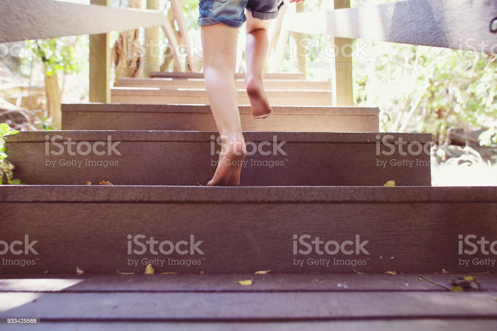 Girl running up wooden steps outdoors at full speed stock photo