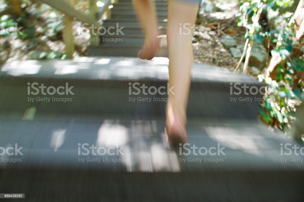 Girl running up wooden steps outdoors blurry stock photo