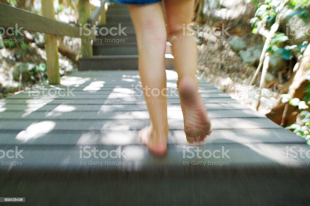 Girl running up wooden steps outdoors closer stock photo