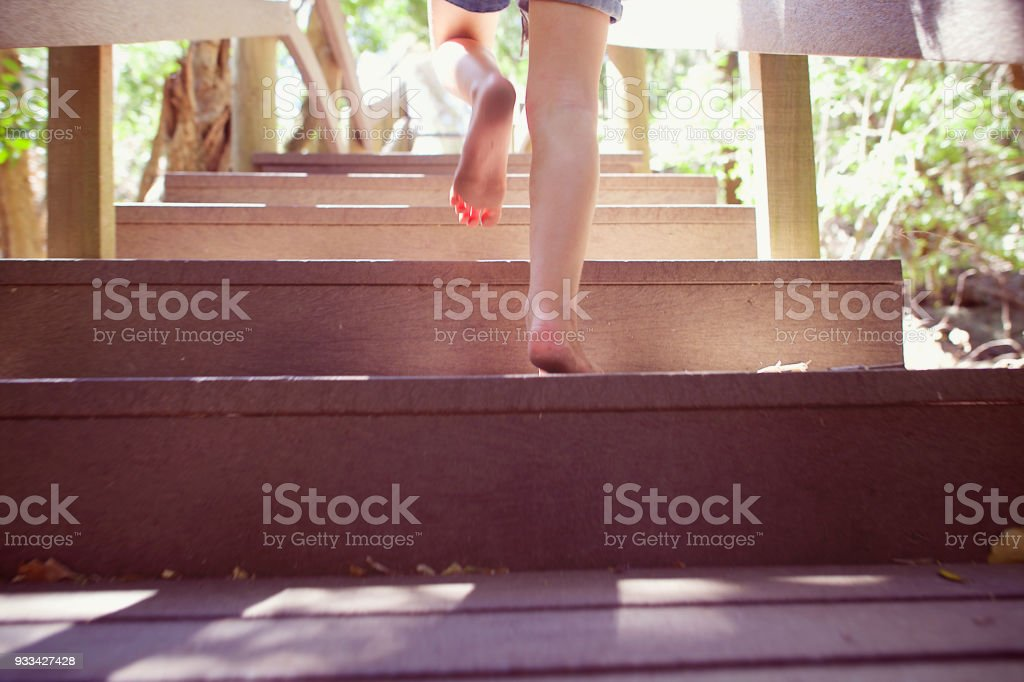 Girl running up wooden steps outdoors dirty bare foot stock photo