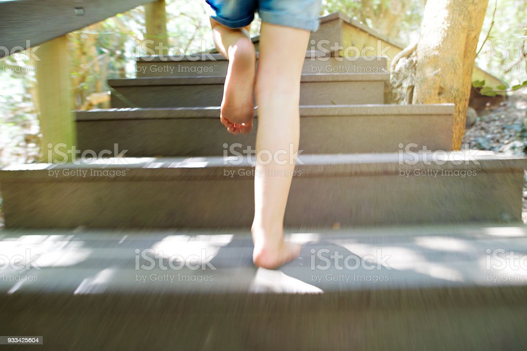 Girl running up wooden steps outdoors Movement stock photo