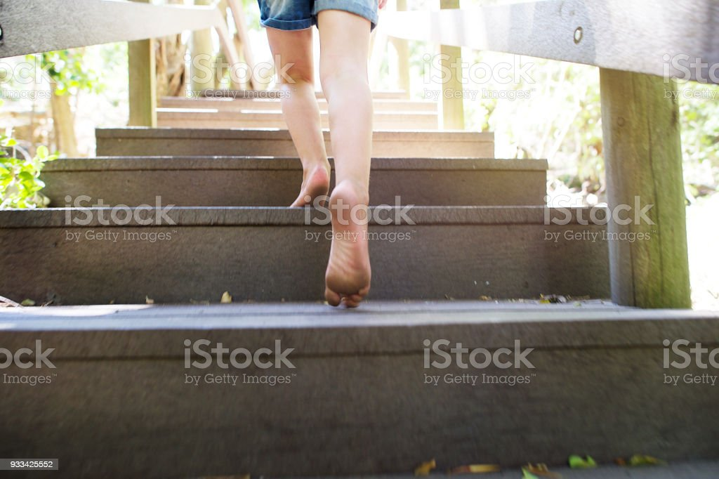 Girl running up wooden steps outdoors Moving Up stock photo