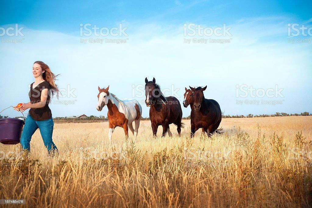 Girl Running With Horses stock photo