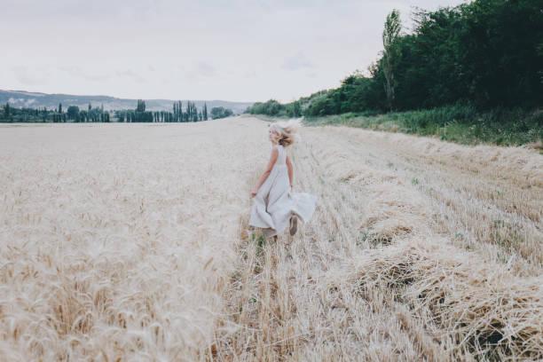 Girl runs along a wheat field. stock photo