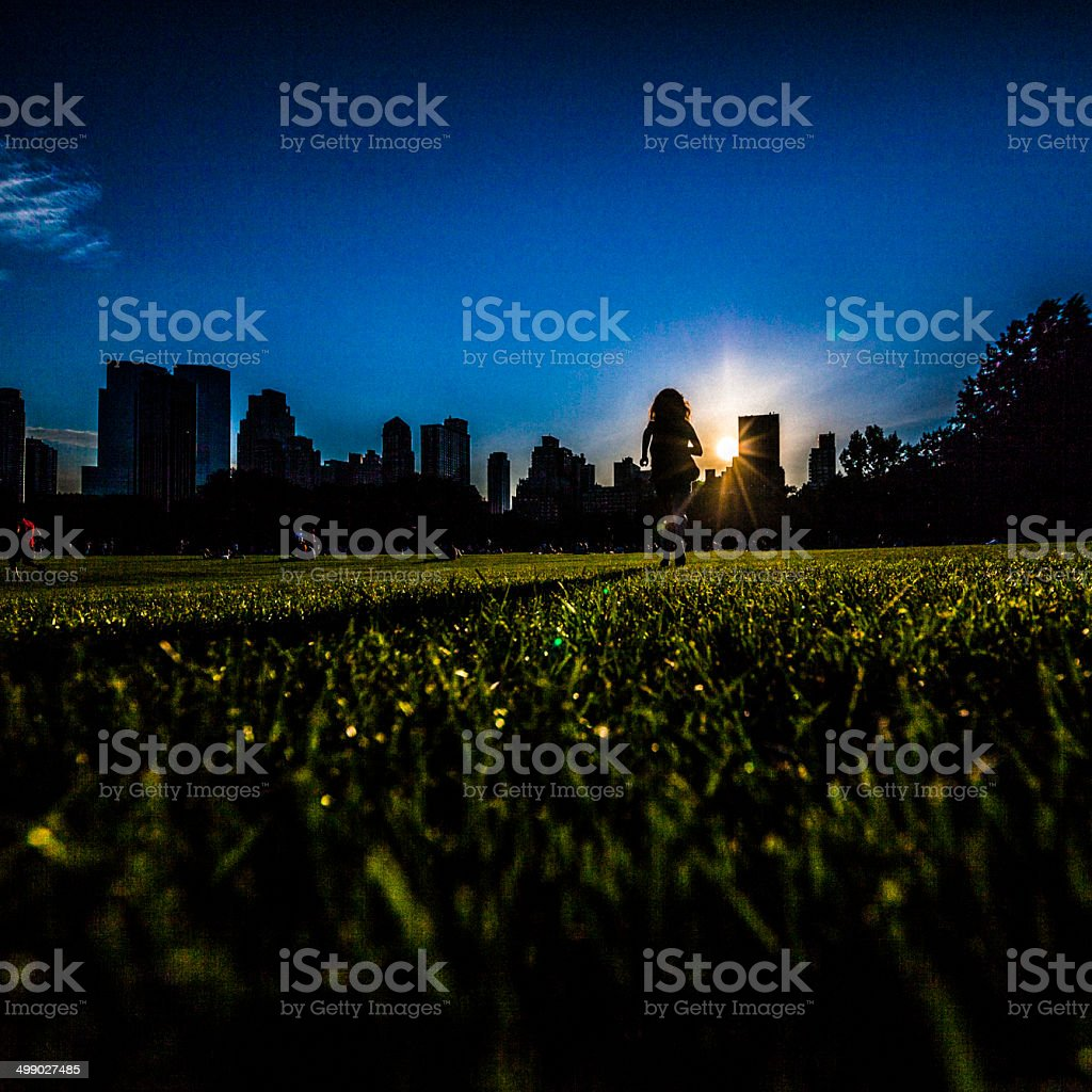 Girl runs in front of Manhattan skyline in Central Park royalty-free stock photo