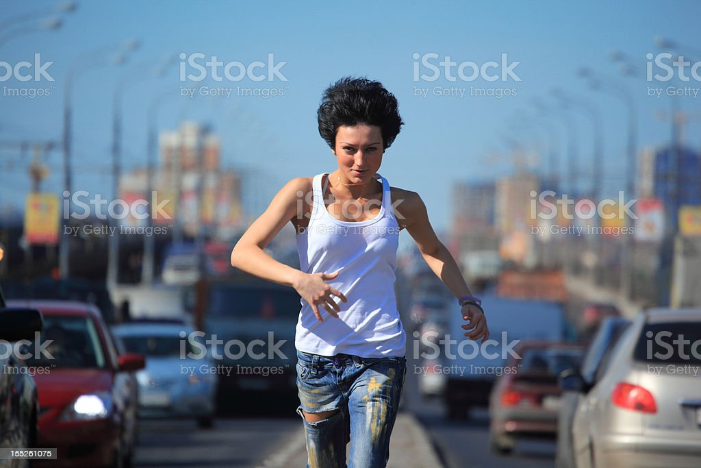 Girl runs on highway middle in city stock photo