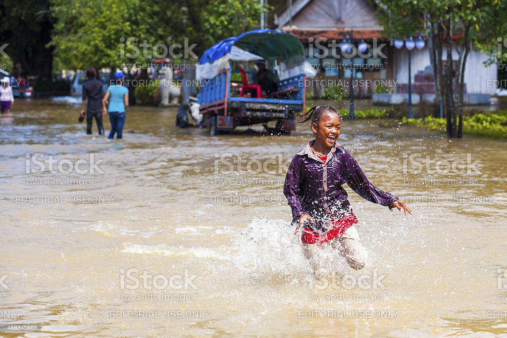 Girl runs through floodwaters, Siem Reap, Cambodia stock photo