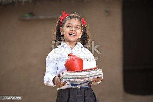 Little girl saving money in piggy bank for future education