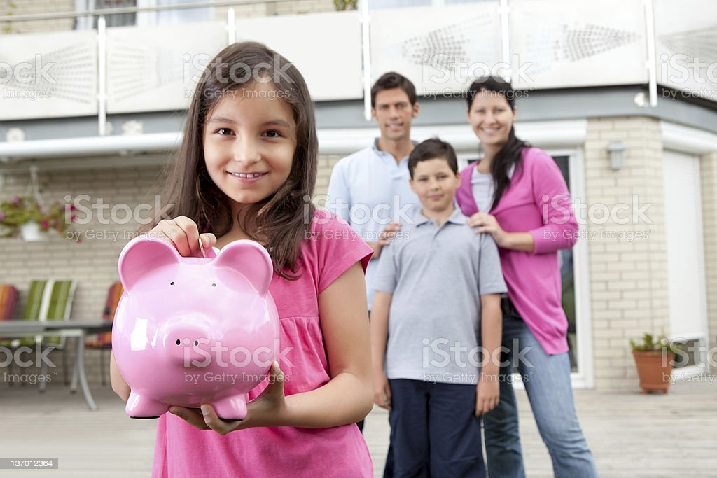 Girl saving money with family at the back royalty-free stock photo