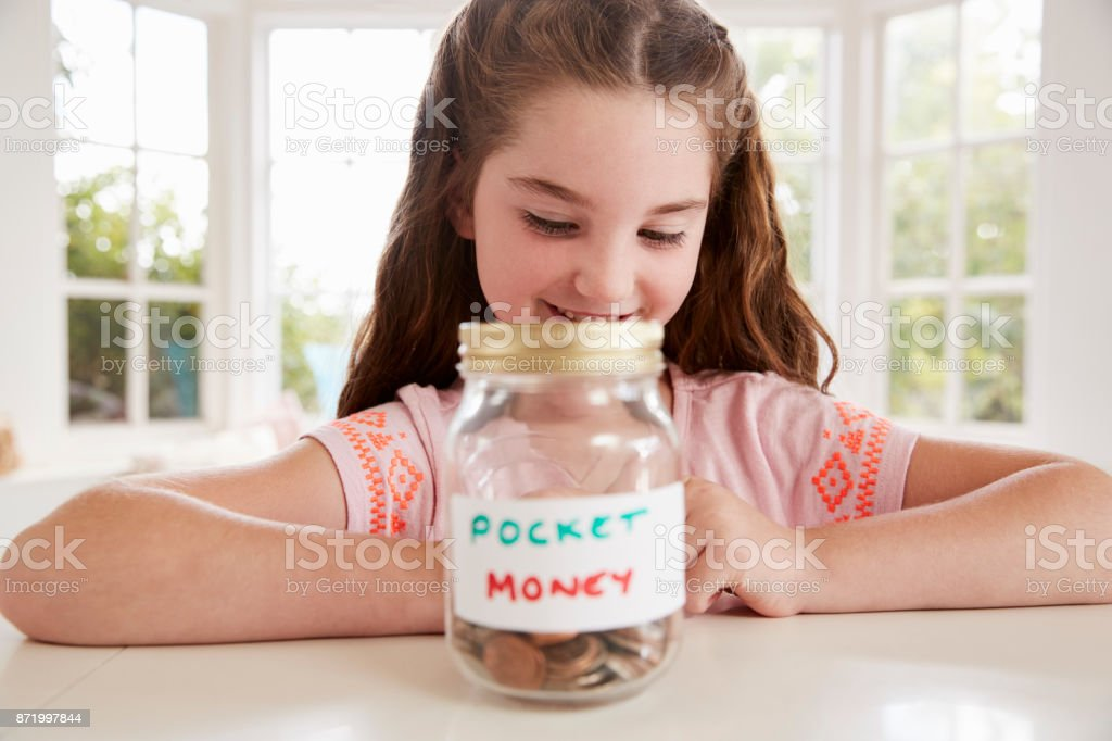 Girl Saving Pocket Money In Glass Jar At Home stock photo